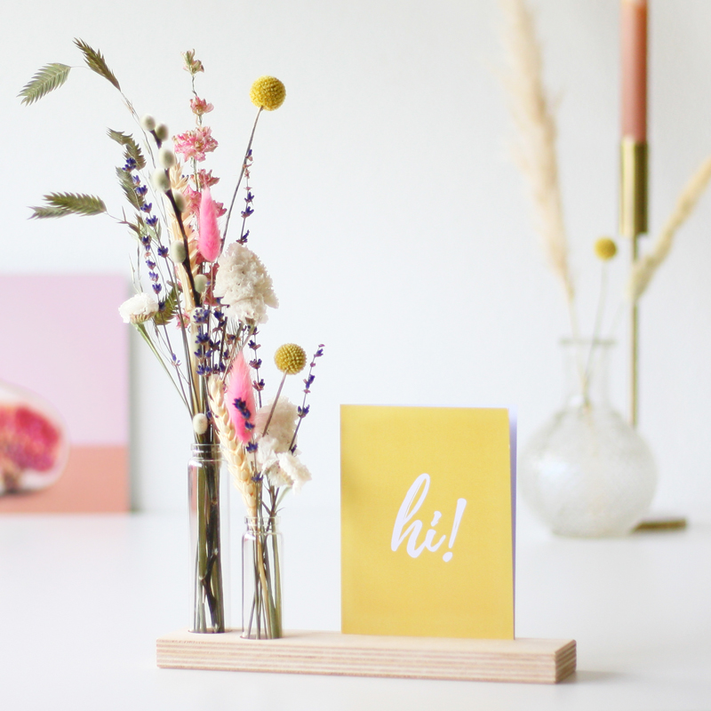 Wooden base holding two glass vials full of pink, lilac, white and yellow dried flowers, with yellow greeting card reading 'hi!'.