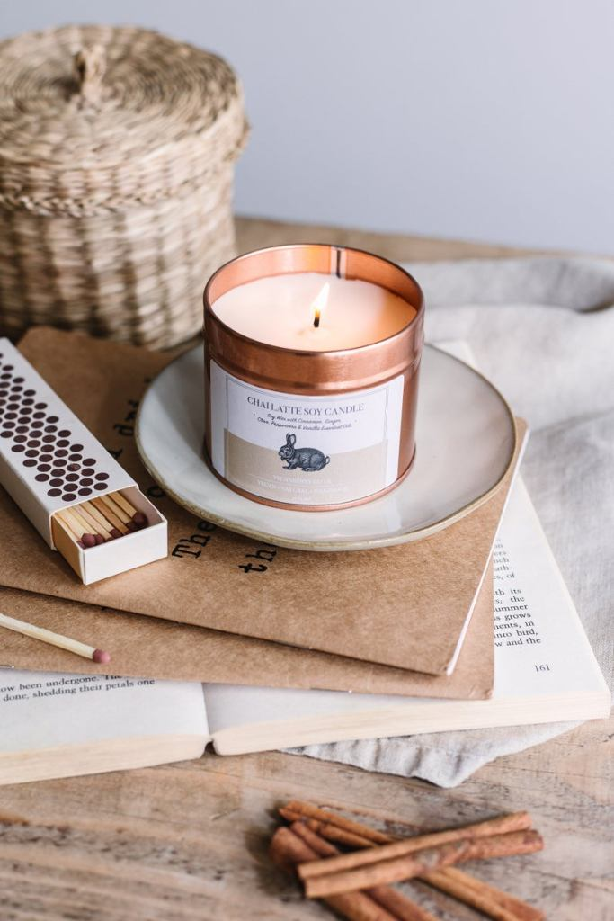 Photo of cream candle in a copper jar, sat upon a white saucer upon an opened book, surrounded by matches and cinnamon sticks.