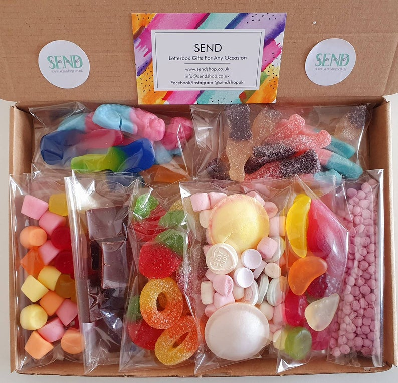 Ariel view of a rectangular cardboard box with plastic packets of assorted pick n mix sweets