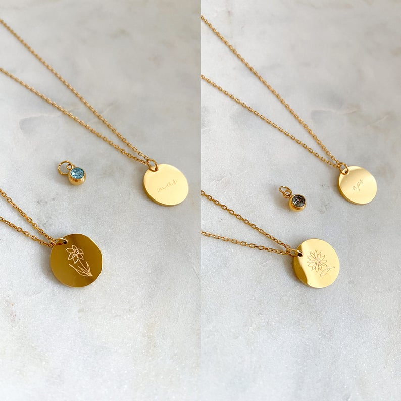 Photo of two gold disc pendants engraved with a birth month flower, and accompanied with a matching birthstone.