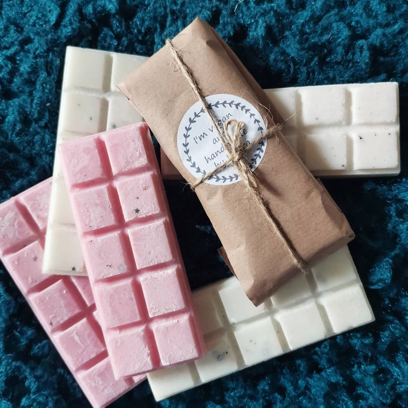 Photo of pink and white wax melt bars, one is wrapped in brown paper tied with string.
