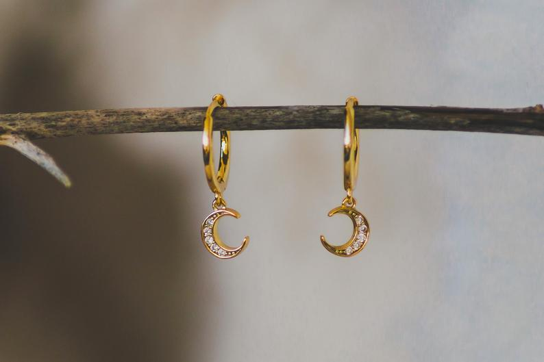 Photo of two dainty gold hoop earrings with rhinestone crescent moon charms dangling from them.