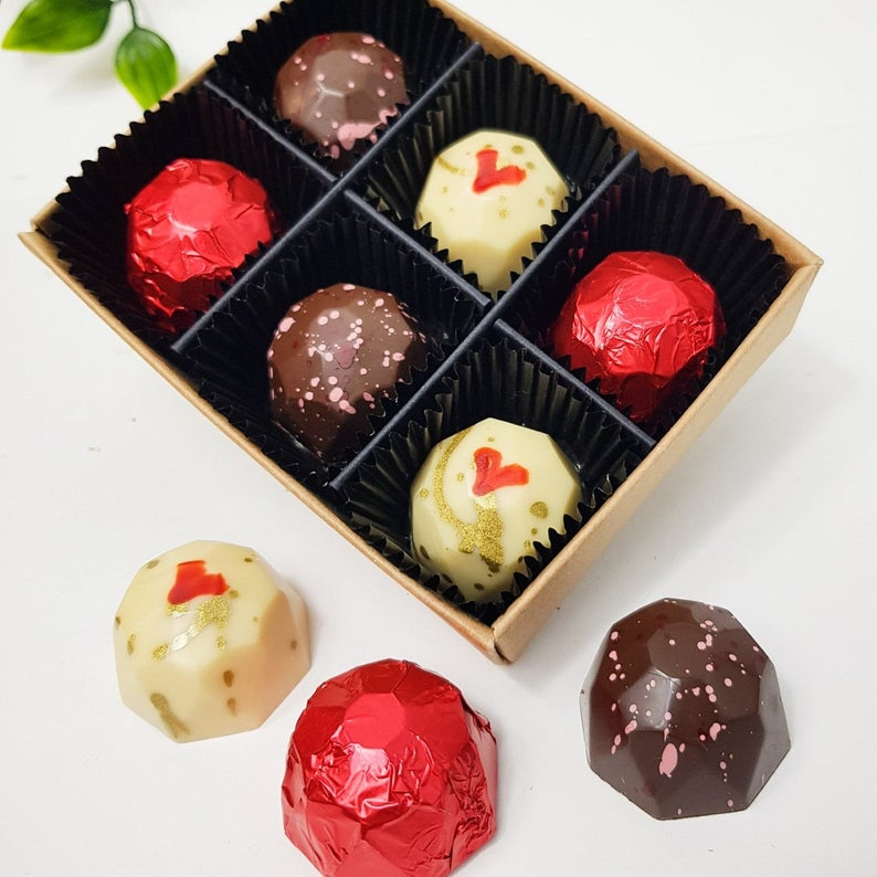 Photo of a box of 6 chocolates, in an assortment of milk chocolate, white chocolate, and red foil chocolates with gold gilding.
