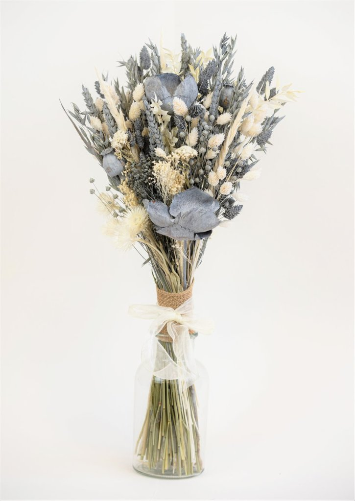 Dried neutral and green-grey flowers, grasses, and foliage in a clear glass vase.