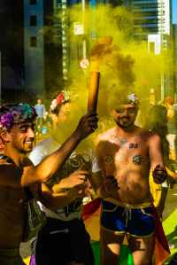 Photo of three male presenting people celebrating LGBTQ+ pride wearing rainbow flower crowns, body glitter, and flags. They're smiling widely waving yellow smoke wands.
